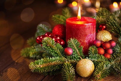 Bild vergrößern: Burning candle in festive christmas arrangement